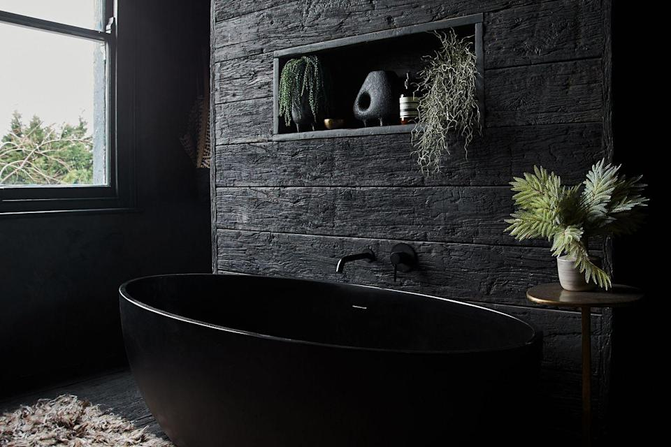 """<p>""""I wanted to add as much texture as possible to my bathroom, so I clad the wall in faux wooden planks from <a href=""""https://millboard.co.uk/samples?gclid=Cj0KCQjw9_mDBhCGARIsAN3PaFOn_tXpiKQHHDqLdfDAS2tiQN5Bv65ldpk41_rL88w2_ga5df0UJ0IaAmccEALw_wcB"""" rel=""""nofollow noopener"""" target=""""_blank"""" data-ylk=""""slk:Millboard"""" class=""""link rapid-noclick-resp"""">Millboard</a>. They're intended to be used outside but I love the texture. I then accessorised with plants and rugs. The walls are all plastered with Tadelakt, a Moroccan waterproof plaster. The bath is stone.""""</p>"""