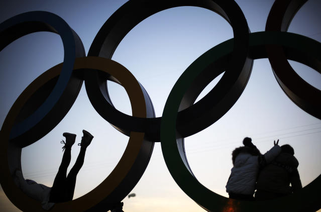 Spectators pose for photos after climbing up into the Olympic rings at the 2014 Winter Olympics, Friday, Feb. 21, 2014, in Sochi, Russia. (AP Photo/David Goldman)