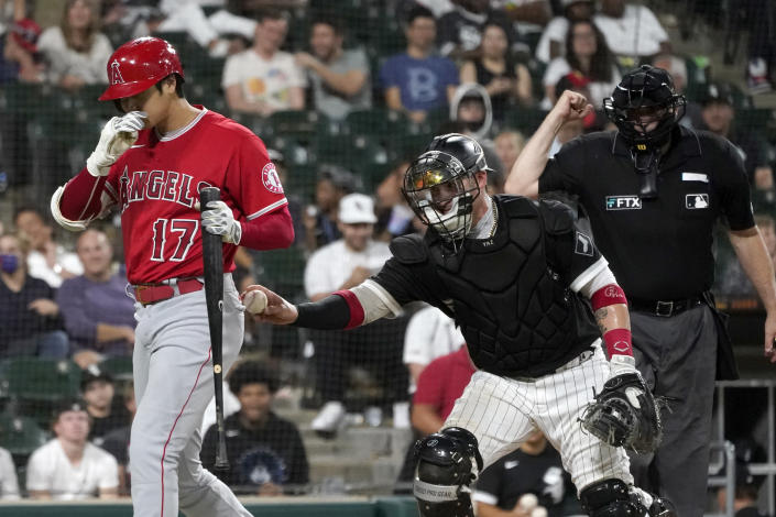 Chicago White Sox catcher Yasmani Grandal, center, tags out Los Angeles Angels' Shohei Ohtani after a dropped third strike, as home plate umpire Bill Welke makes the call during the ninth inning of a baseball game Tuesday, Sept. 14, 2021, in Chicago. The White Sox won 9-3. (AP Photo/Charles Rex Arbogast)