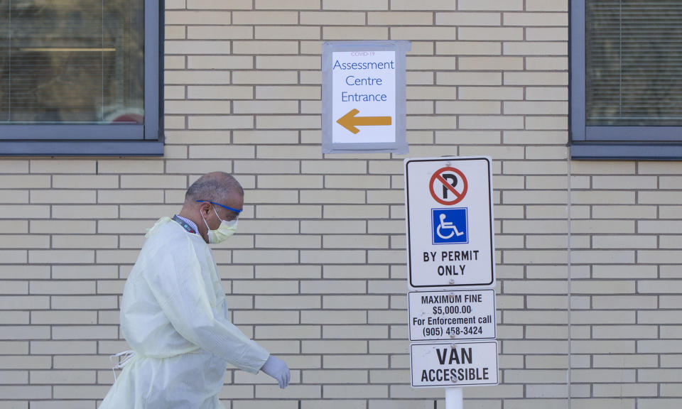 BRAMPTON, March 15, 2020 -- A medical worker wearing protective gear walks past a direction sign of a COVID-19 assessment center at Peel Memorial Center for Integrated Health and Wellness in Brampton, Ontario, Canada, on March 15, 2020. Canada's Ontario provincial government reported 39 new cases of COVID-19 Sunday morning, increasing the provincial total to 142. (Photo by Zou Zheng/Xinhua via Getty) (Xinhua/Zou Zheng via Getty Images)