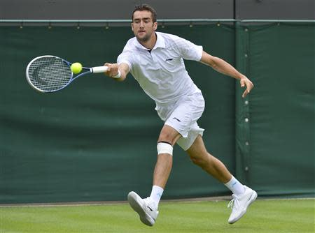 Marin Cilic of Croatia hits a return to Marcos Baghdatis of Cyprus in their men's singles tennis match at the Wimbledon Tennis Championships, in London