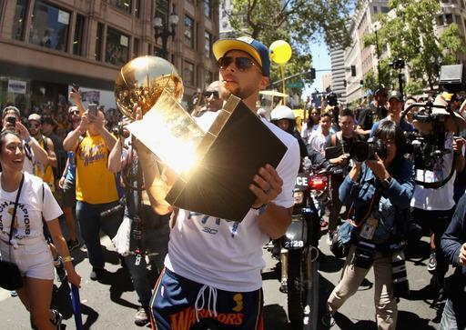 OAKLAND, CA - JUNE 12: Stephen Curry #30 of the Golden State Warriors celebrates with the championship trophy during the Golden State Warriors Victory Parade on June 12, 2018 in Oakland, California. The Golden State Warriors beat the Cleveland Cavaliers 4-0 to win the 2018 NBA Finals. (Photo by Ezra Shaw/Getty Images)