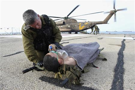 An Israeli army officer speaks to a soldier who was wounded during an explosion as he is evacuated to hospital, in the northern city of Haifa