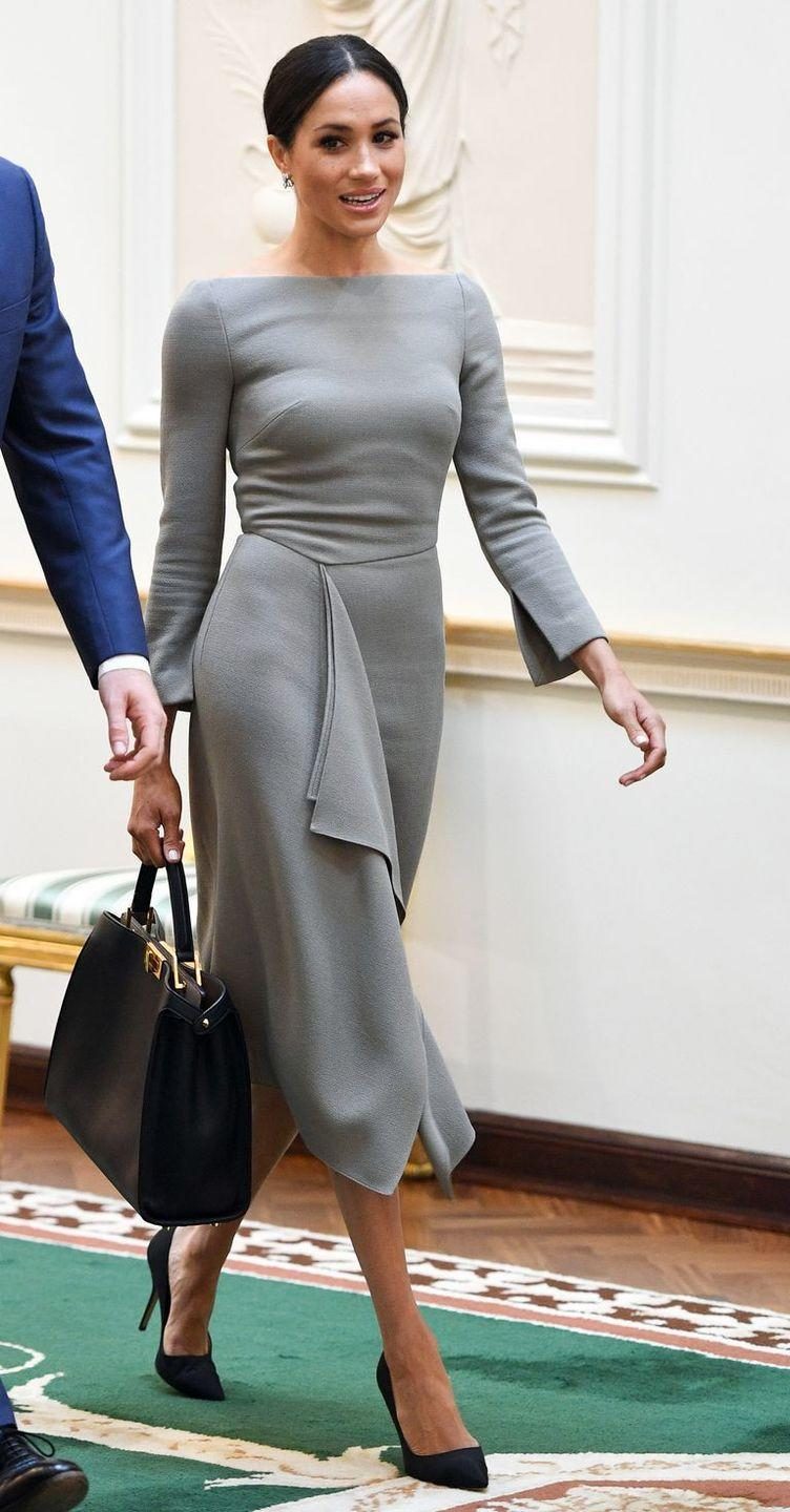 """<p>During her visit to Ireland, the former actress wore a stunning grey <a href=""""https://www.net-a-porter.com/gb/en/Shop/Search?keywords=roland+mouret&termUsed=roland+mouret"""" rel=""""nofollow noopener"""" target=""""_blank"""" data-ylk=""""slk:Roland Mouret"""" class=""""link rapid-noclick-resp"""">Roland Mouret</a> dress, a version of which she first wore on the night before her wedding. She teamed the look with black high heel shoes and a black tote bag. </p>"""