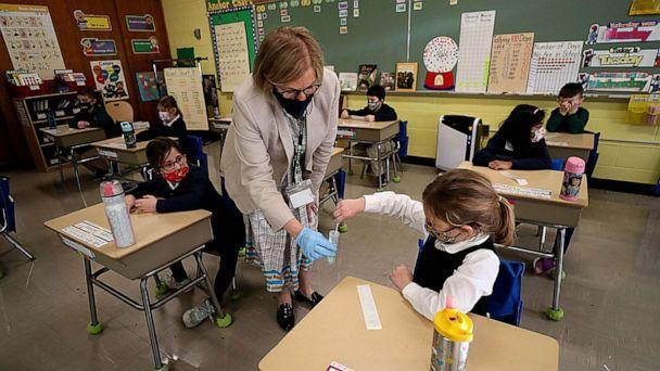 PHOTO: A student gives her COVID-19 swab to Dr. Helenann Civian, the principal of South Boston Catholic Academy in Boston, Jan. 19, 2021. (Suzanne Kreiter/The Boston Globe via Getty Images)