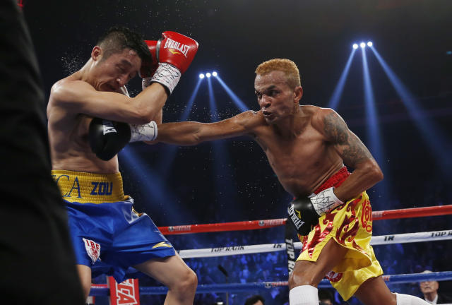 China's double Olympic gold medalist Zou Shiming, left, fights with Thailand's Amnat Ruenroeng during their IBF flyweight title belt boxing match at the Venetian Macao in Macau, Saturday, March 7, 2015. Ruenroeng won the IBF flyweight title belt boxing match. (AP Photo/Kin Cheung)