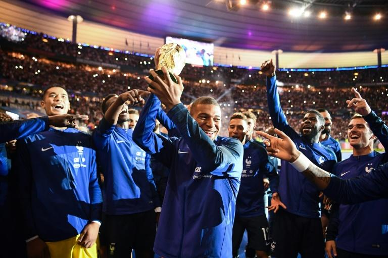 Kylian Mbappe and his France teammates parade the World Cup trophy after their win over the Netherlands
