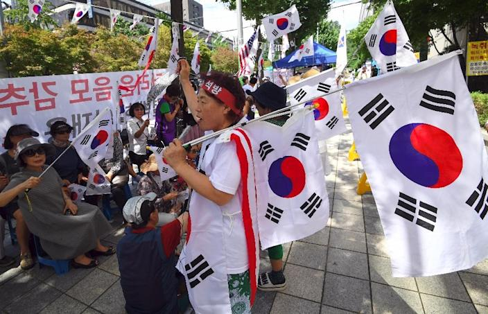 Supporters of South Korea's ousted president Park Geun-Hye wave national flags during a rally demanding the release of Samsung heir Lee Jae-Yong (AFP Photo/JUNG Yeon-Je)