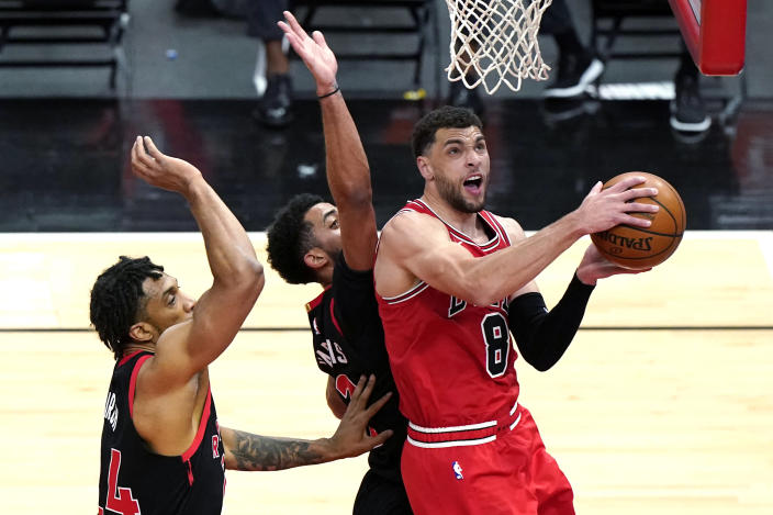 Chicago Bulls guard Zach LaVine, right, drives to the basket against Toronto Raptors center Khem Birch, left, and guard Jalen Harris during the first half of an NBA basketball game in Chicago, Thursday, May 13, 2021. (AP Photo/Nam Y. Huh)