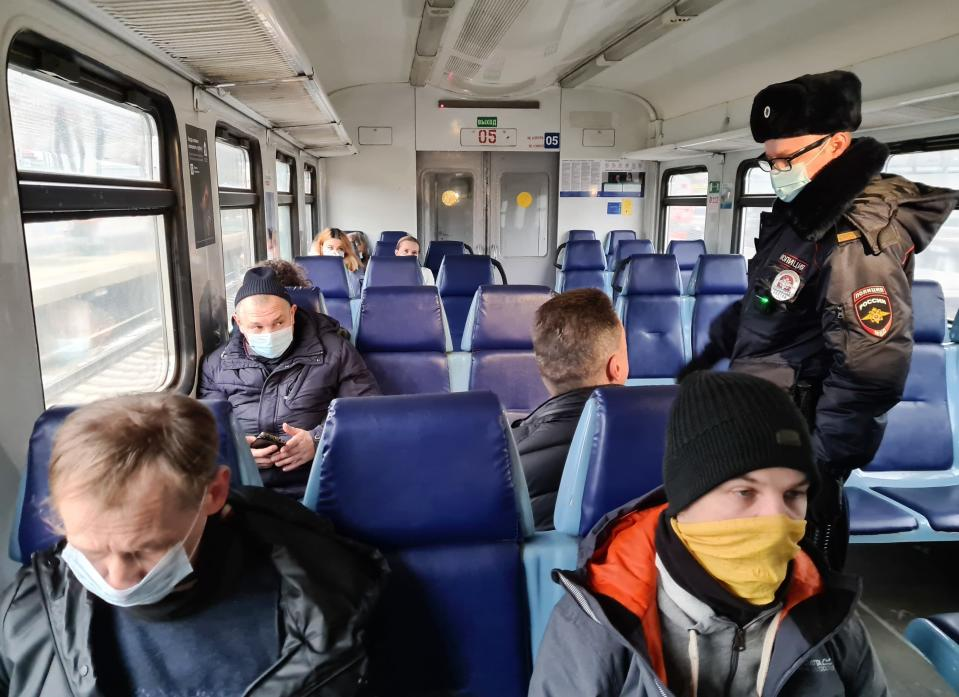 A Russian police officer checks public adherence of the 'mask regime' forcing people to wear masks in public places, in an electric train car in Moscow, Russia, Friday, Nov. 27, 2020. Russia has registered a sharp spike in coronavirus cases Friday, with officials reporting 27,543 new confirmed infections, which is over 2,000 contagions more than the day before and the highest in the pandemic. (Denis Voronin, Moscow News Agency photo via AP)