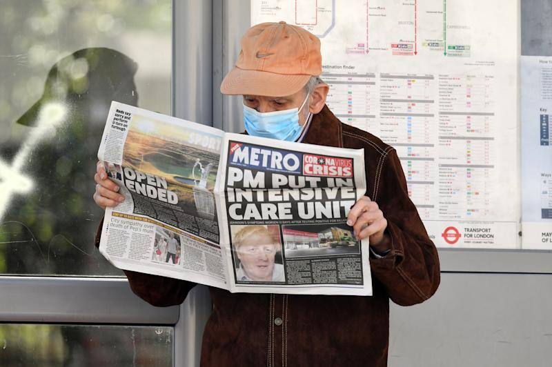 A man wearing a facemask at a bus stop reading a newspaper outside St Thomas' Hospital in Central London where Prime Minister Boris Johnson is in intensive care as his coronavirus symptoms persist.