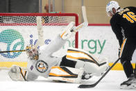 Pittsburgh Penguins goalie Alex D'Orio attempts to block a shot by Jason Zucker (16) during the team's first NHL hockey practice of the season in Cranberry, Pa., Thursday, Sept. 23, 2021. (AP Photo/Gene J. Puskar)