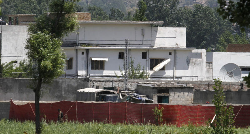 FILE - In this May 2, 2011 file photo, a Pakistani soldier stands near a compound where al-Qaida leader Osama bin Laden lived in Abbottabad, Pakistan. Bin Laden was able to live in Pakistan undetected for nine years because of a breathtaking scale of negligence and incompetence at practically all levels of the Pakistani government, according to an official government report published by the pan-Arab Al-Jazeera satellite channel on Monday, July 8, 2013. (AP Photo/Anjum Naveed, File)