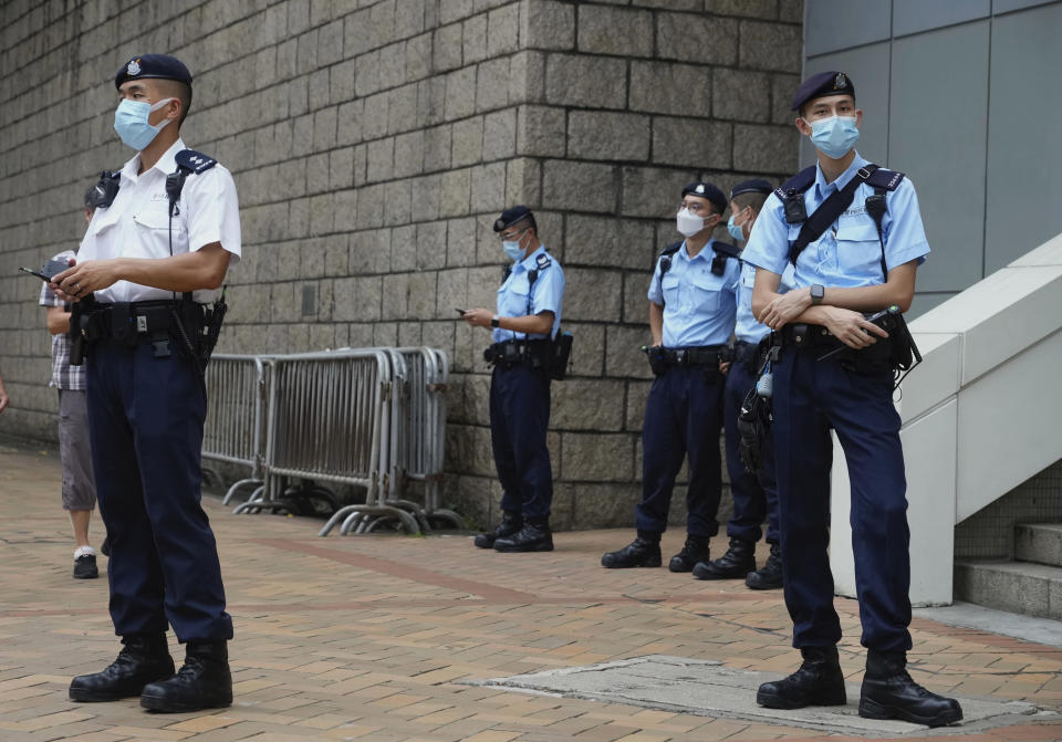 Police officers stand guard as they wait for Tong Ying-kit to leave a court in Hong Kong Tuesday, July 27, 2021. Tong, 24, the first person to be tried under Hong Kong's sweeping national security law was found guilty of secessionism and terrorism on Tuesday in a ruling condemned by human rights activists. (AP Photo/Vincent Yu)