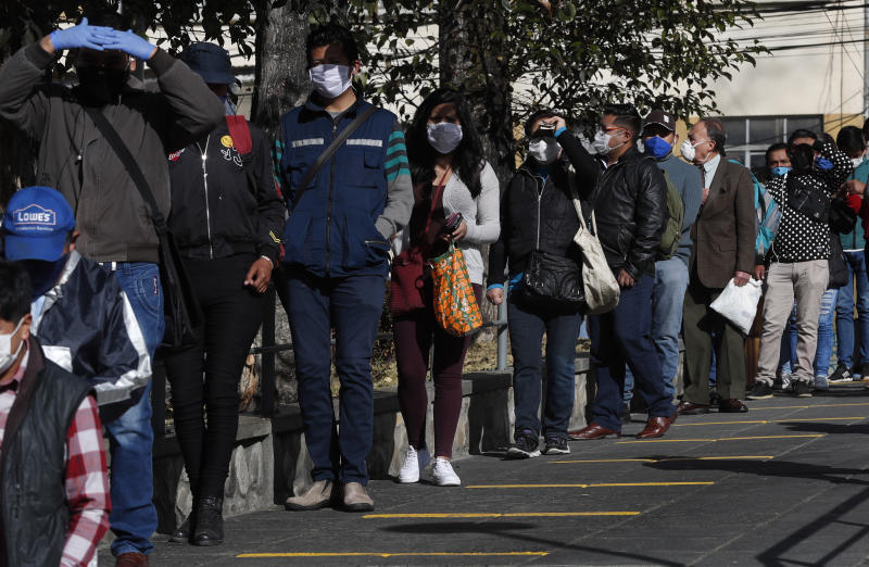 Commuters wearing masks as a precaution against the spread of the new coronavirus line up, keeping distance, at a cable car station in La Paz, Bolivia, Monday, June 1, 2020. The cable restarted operations, with a reduced number of passengers per gondola,  as the total lockdown begins to ease. (AP Photo/Juan Karita)