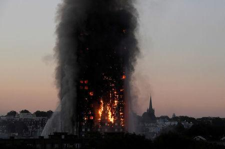 Flames and smoke billow as firefighters deal with a serious fire in the Grenfell Tower apartment block at Latimer Road in West London, Britain June 14, 2017. REUTERS/Toby Melville/File Photo