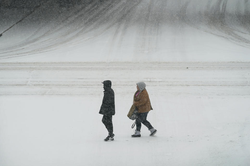 Pedestrians cross a snow covered street, Monday, Jan. 25, 2021, in downtown Des Moines, Iowa. A major winter storm is expected to blanket a large swath of the middle of the country with snow Monday and disrupt travel as more than a foot of snow falls in some areas. (AP Photo/Charlie Neibergall)