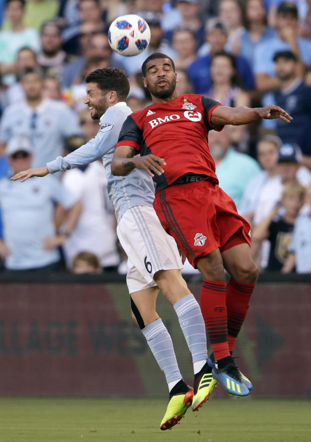 Sporting Kansas City midfielder Ilie Sanchez (6) heads the ball next to Toronto FC forward Jordan Hamilton, right, during the first half of an MLS soccer match in Kansas City, Kan., Saturday, July 7, 2018. (AP Photo/Orlin Wagner)