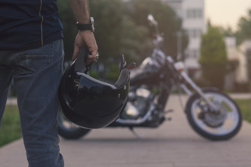 Man with motorcycle helmet and a bike in the background.