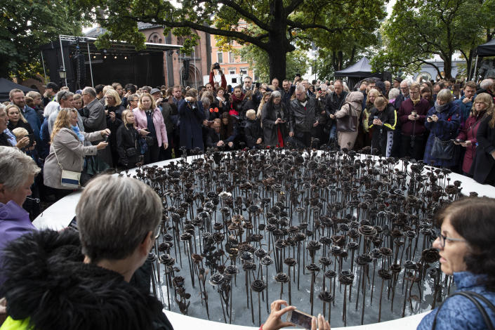 """FILE - In this Saturday, Sept. 28, 2019 file photo, people look at the newly unveiled memorial """"Iron roses"""" is unveiled outside Oslo Cathedral, in Oslo. The memorial is in memory of the 77 people who lost their lives on July 22, 2011 during a bombing and shooting attacks. At 3.25 p.m. on July 22, 2021, a ray of sun should have illuminated the first of 77 bronze columns on a lick of land opposite Utoya island outside Oslo. Over the next 3 hours and 8 minutes, it would have brushed each column in turn, commemorating every person killed by right-wing terrorist Anders Breivik. But on the ten-year anniversary of the terror, the memorial remains a construction site. (Terje Bendiksby/NTB Scanpix via AP, File)"""