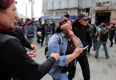 A police officer detains a protester as she and others attempt to defy a ban and to gather at Taksim Square to celebrate May Day, in central Istanbul