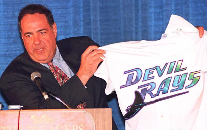 """PALM BEACH, FL - MARCH 9: Vince Naimoli, owner of the """"Tampa Bay Devil Rays"""" displays his new team's jersey to reporters 09 March in Palm Beach, Florida. Members of the Major League Expansion Committee announced Naimoli's team would be one of two new expansion teams approved for baseball. The new team will begin playing in the 1998 season. (COLOR KEY: Background is blue.) AFP PHOTO (Photo credit should read DOUG COLLIER/AFP/Getty Images)"""