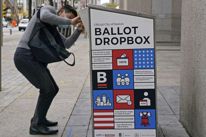 """A voter makes sure his ballot falls into the ballot drop box outside the Boston Public Library, Monday, Oct. 26, 2020, in Boston. Massachusetts election officials say a fire was set in the ballot drop box Sunday, holding more than 120 ballots in what appears to have been a """"deliberate attack."""" The FBI says it is investigating. (AP Photo/Elise Amendola)"""