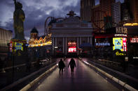 People walk along the Las Vegas Strip devoid of the usual crowds after casinos were ordered to shut down due to the coronavirus outbreak, Wednesday, March 18, 2020, in Las Vegas. (AP Photo/John Locher)