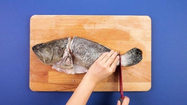 Cutting head and tail off grouper with a knife
