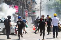 Tear gas and fire extinguisher gas float around demonstrators as they run away from police during a protest against the military coup in Yangon