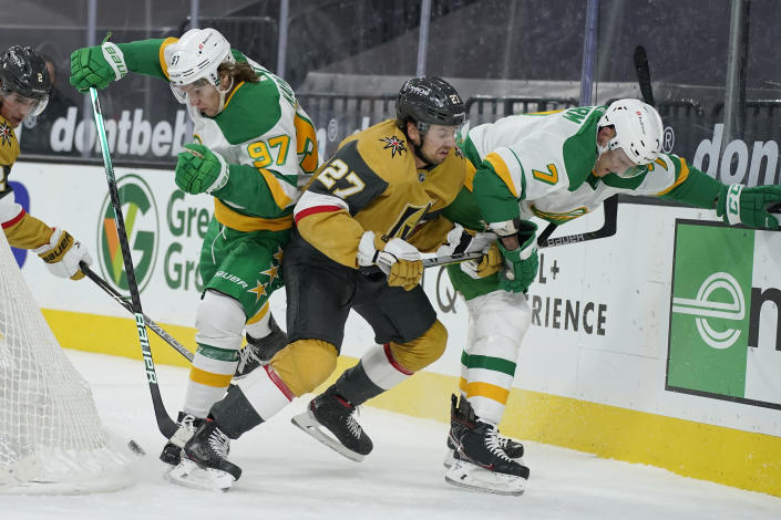 Minnesota Wild center Nico Sturm (7), Vegas Golden Knights defenseman Shea Theodore (27) and left wing Kirill Kaprizov (97) battle for the puck during the first period of an NHL hockey game Wednesday, March 3, 2021, in Las Vegas. (AP Photo/John Locher)