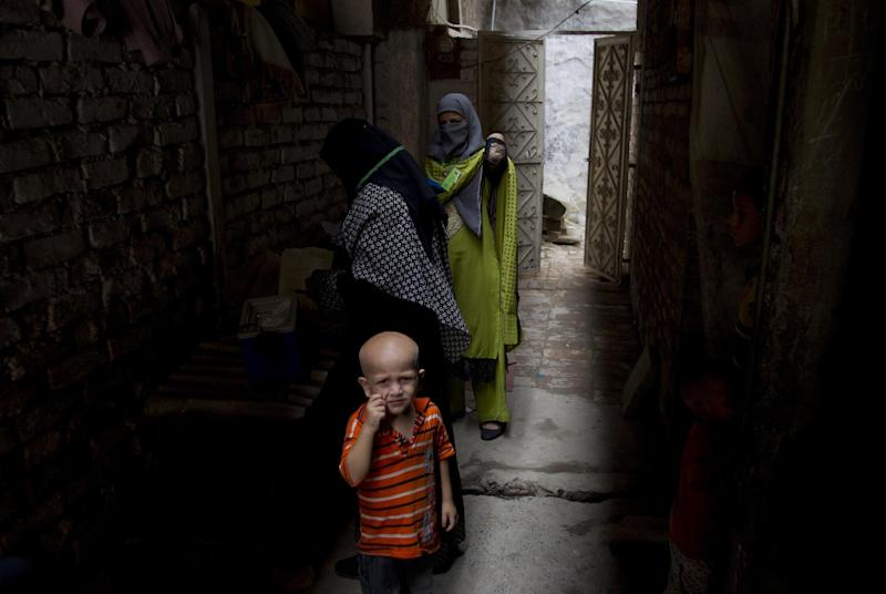 In this Tuesday, Aug. 27, 2013 photo, Pakistani health workers visit Rawalpindi slums to immunize children against polio in Pakistan. Local health authorities confirmed five new polio cases from tribal areas where Islamic militants banned the vaccine over a year ago and many more suspected cases _ one of a series of outbreaks this year in parts of the country where security threats have kept out vaccination teams. (AP Photo/B.K. Bangash)