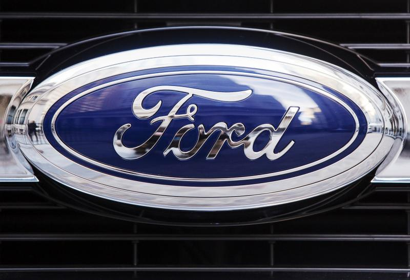 A Ford logo is seen on the grill of a 2015 F-150 truck outside the New York Stock Exchange in New York in this file photo taken January 13, 2014. Ford Motor Co posted lower-than-expected first-quarter profit on Friday as the No. 2 U.S. automaker saw higher warranty costs in North America for older vehicles by $400 million, sending shares down 2 percent in premarket trading. REUTERS/Lucas Jackson/Files (UNITED STATES - Tags: TRANSPORT BUSINESS)