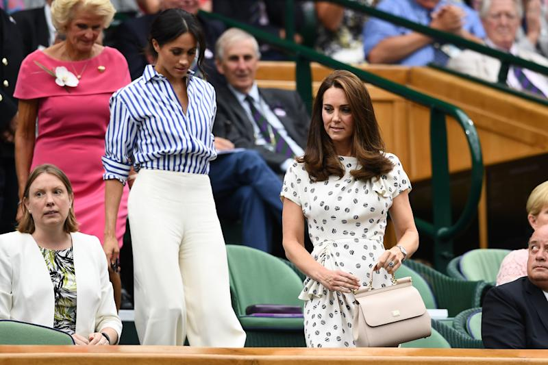 Catherine Duchess of Cambridge (R) and Meghan, Duchess of Sussex visit Day 12 of the Wimbl Edon Lawn Tennis Championships at All England Lawn Tennis and Croquet Club on July 14, 2018 in London, England.