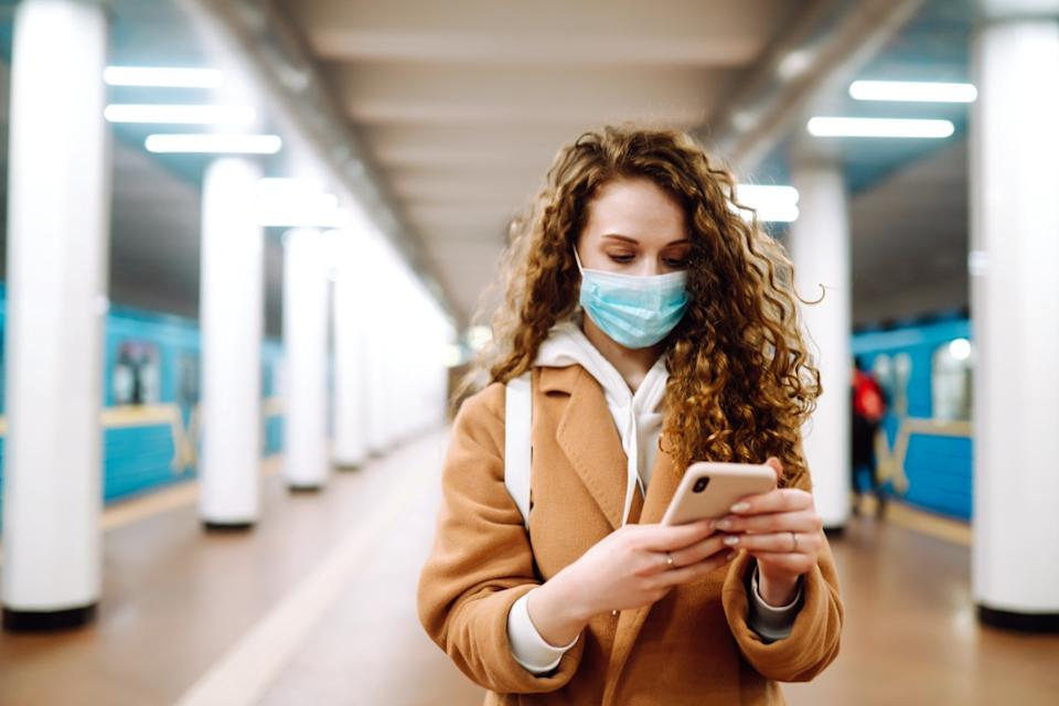 Girl in protective sterile medical mask with a phone at subway station