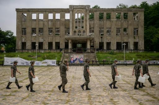 South Korean soldiers walk past the former North Korean Workers Party headquarters in Cheorwon