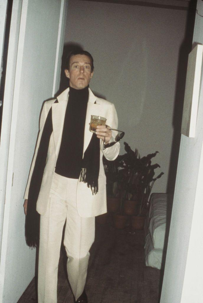 <p>Here, Halston is photographed candidly in a chic suit and black turtleneck.</p>