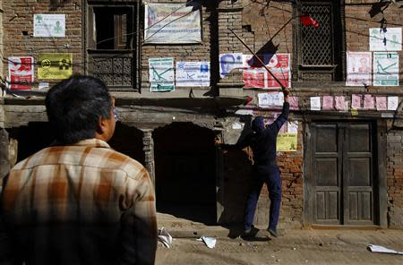 A police personnel recruited for the Constituent Assembly election, removes a party flag near the polling station a day before the election in Bhaktapur