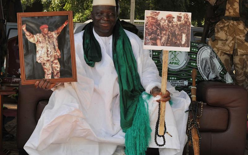 Yahya Jammeh poses with pictures of himself in military outfits in 2011 - Credit: AFP