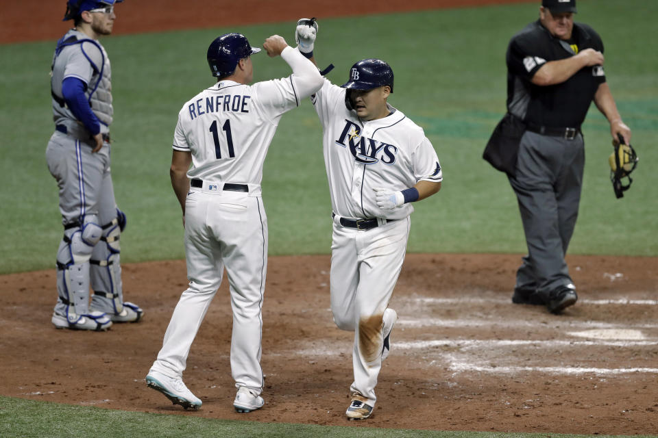 Tampa Bay Rays' Yoshitomo Tsutsugo, of Japan, second from right, celebrates with Hunter Renfroe (11) after Tsutsugo hit a two-run home run off Toronto Blue Jays starting pitcher Hyun-Jin Ryu during the fifth inning of a baseball game Friday, July 24, 2020, in St. Petersburg, Fla. Looking on is Blue Jays catcher Danny Jansen. (AP Photo/Chris O'Meara)
