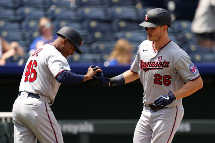 Minnesota Twins' Max Kepler (26) celebrates with third base coach Tony Diaz after hitting a solo home run during the sixth inning of a baseball game against the Kansas City Royals Sunday, July 4, 2021, in Kansas City, Mo. (AP Photo/Charlie Riedel)