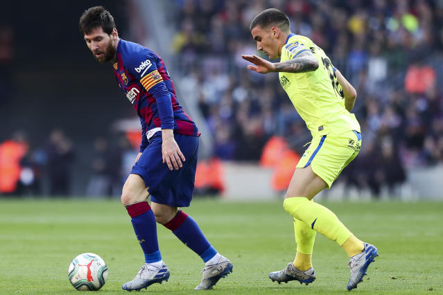 Barcelona's Lionel Messi, left, controls the ball under pressure from Getafe's Mauro Arambarri during a Spanish La Liga soccer match between Barcelona and Getafe at the Camp Nou stadium in Barcelona, Spain, Saturday Feb. 15, 2020. (AP Photo/G.Garin)