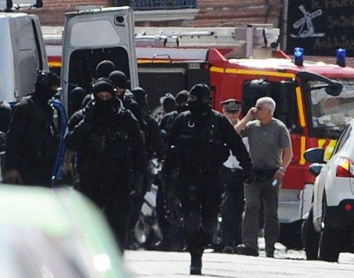 French rapid-intervention GIPN police units leave the area after police stormed a bank in Toulouse