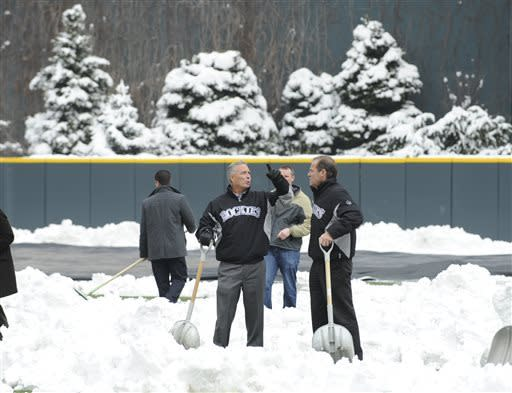 Dan O'Dowd, Executive Vice President, Chief Baseball Officer/General Manager and Colorado Rockies owner Dick Monfort, right, survey the snow while shoveling before the start of a baseball doubleheader between the New York Mets and the Colorado Rockies on Tuesday, April 16, 2013, in Denver. (AP Photo/Jack Dempsey)