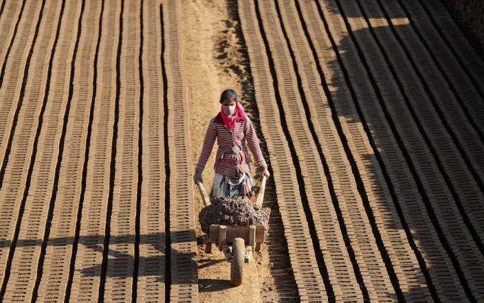 An Indian woman laborer works at a brick factory was allowed to resume during lockdown to control the spread of the coronavirus outskirts of Jammu, India, Wednesday, April 22, 2020. India has reported nearly 20,000 confirmed cases of COVID-19 and over 600 deaths.(AP Photo/ Channi Anand)