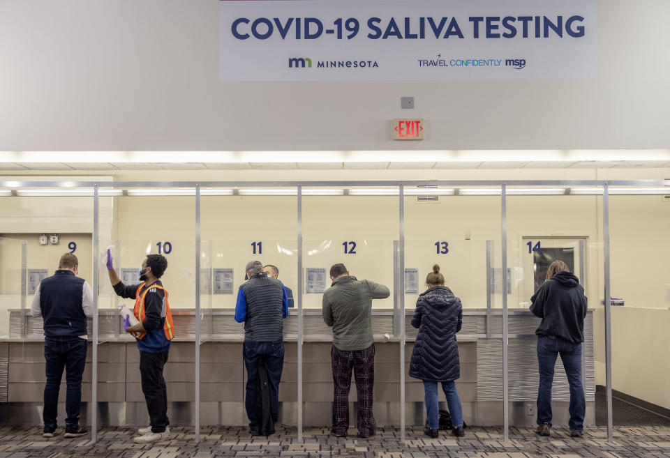 FILE - In this Nov. 12, 2020, file photo, people get tested at the new saliva COVID-19 testing site at the Minneapolis-St. Paul International Airport. With the coronavirus surging out of control, the nation's top public health agency advised Americans on Thursday, Nov. 19, not to travel for Thanksgiving and not to spend the holiday with people from outside their household. (Elizabeth Flores/Star Tribune via AP, File)