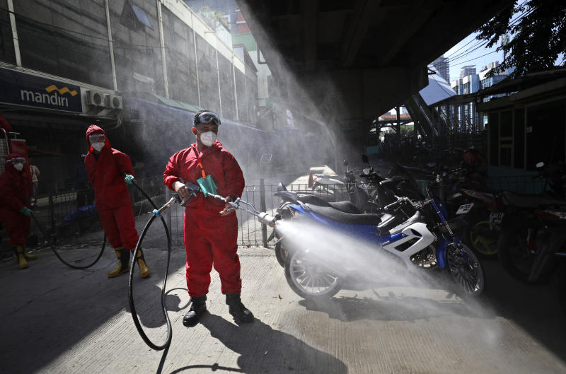 A firemen spray disinfectant to curb the spread of the coronavirus at the Tanah Abang textile market in Jakarta, Indonesia, Thursday, June 4, 2020. Authorities in Indonesia's capital will ease a partial lockdown as the world's fourth most populous nation braces to gradually reopen its economy. (AP Photo/Dita Alangkara)