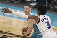 Charlotte Hornets forward Gordon Hayward, left, looks to pass against Minnesota Timberwolves forward Jaden McDaniels during the second half of an NBA basketball game in Charlotte, N.C., Friday, Feb. 12, 2021. (AP Photo/Nell Redmond)