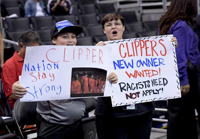 Fans hold up signs in support of the Los Angeles Clippers before Game 5 of an opening-round NBA basketball playoff series between the Clippers and the Golden State Warriors on Tuesday, April 29, 2014, in Los Angeles. NBA Commissioner Adam Silver announced Tuesday that Clippers owner Donald Sterling has been banned for life by the league. (AP Photo)