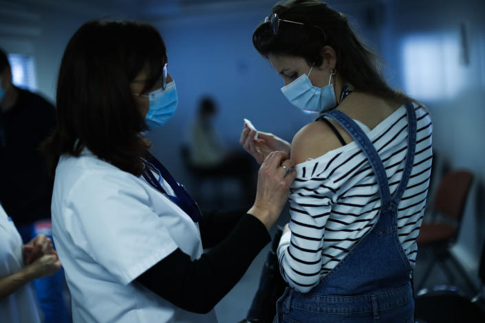 A nurse administrates a Pfizer/Biontech COVID-19 vaccine to a health care worker at the MontLegia CHC hospital in Liege, Belgium, Wednesday, Jan. 27, 2021. (AP Photo/Francisco Seco)